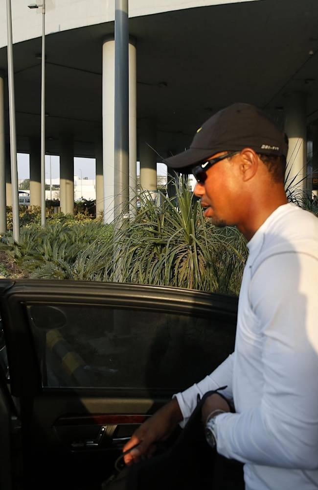 Tiger Woods arrives at the Indira Gandhi International airport in New Delhi, India, Monday, Feb. 3, 2014. Woods arrived Monday on his first visit to India to play an exhibition with a top business executive. (AP Photo /Manish Swarup)