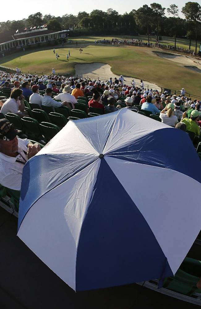 In this image made with a fish eye lens, Fans watch as Dustin Johnson arrives at the 18th hole during the third round of the U.S. Open golf tournament in Pinehurst, N.C., Saturday, June 14, 2014