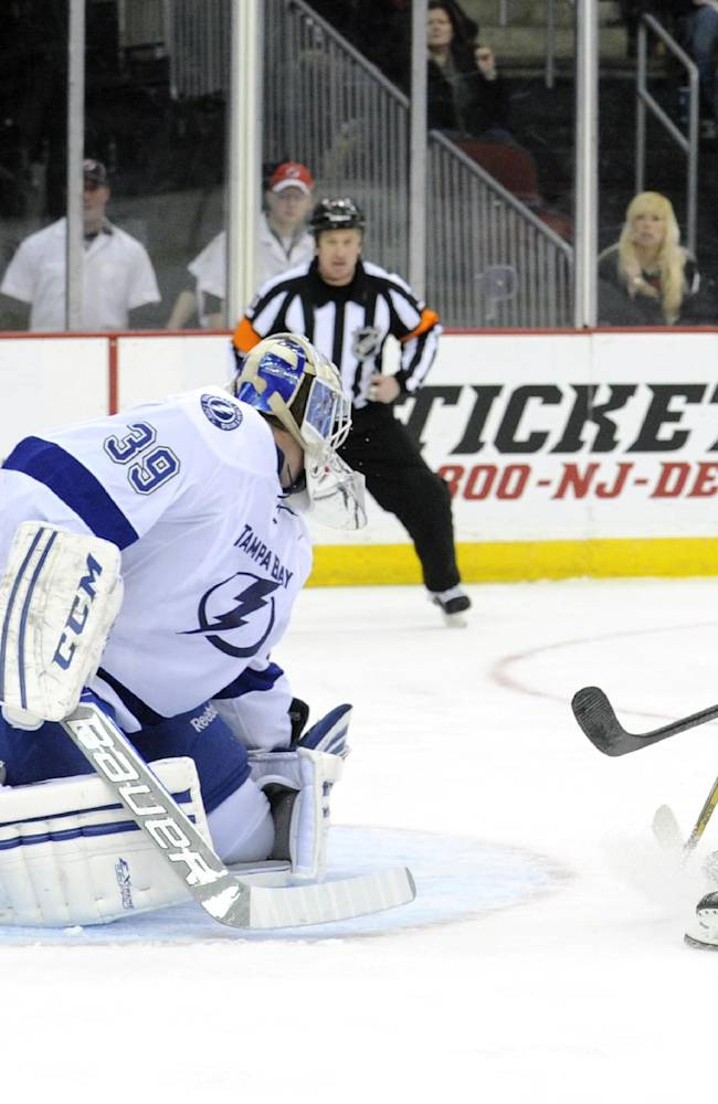 New Jersey Devils' Damien Brunner, right, of Switzerland, scores a goal past Tampa Bay Lightning goaltender Anders Lindback, of Sweden, during the second period of an NHL hockey game Saturday, Dec. 14, 2013, in Newark, N.J