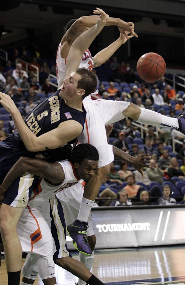 Georgia Tech's Daniel Miller, center, battles Clemson's Rod Hall, bottom, and K.J. McDaniels, back, for a rebound during the second half of an NCAA college basketball game in the second round of the Atlantic Coast Conference men's tournament in Greensboro, N.C., Thursday, March 13, 2014