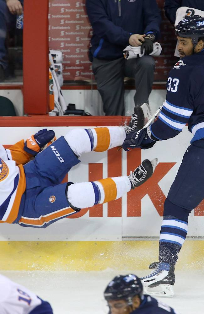 New York Islanders' Thomas Hickey (14) falls to the ice after being checked by Winnipeg Jets' Dustin Byfuglien (33) during the first period of an NHL hockey game in Winnipeg, Manitoba, Tuesday, March 4, 2014