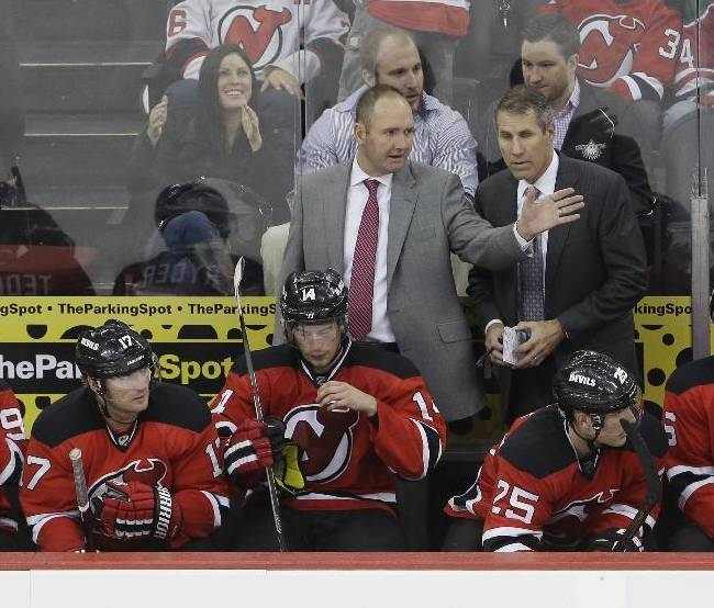 New Jersey Devils head coach Peter DeBoer, top left, talks to assistant coach Dave Barr during the third period of an NHL hockey game against the New York Rangers, Saturday, Oct. 19, 2013, in Newark, N.J. The Devils won 4-0