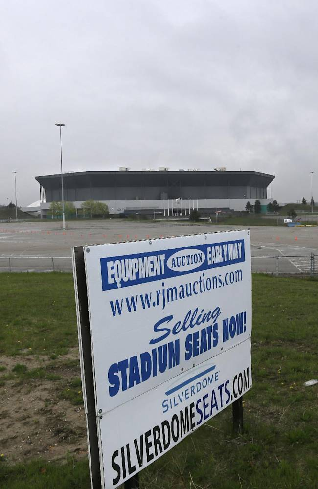In this May 12, 2014 photo, a sign for RJM Auctions is seen outside the Pontiac Silverdome in Pontiac, Mich. The venue is a shell of its former self with its roof in tatters and a lack of electrical power that has left the stadium's innards dark and mold-covered. The Silverdome's current owner is determined to cash in before it's too late, putting everything inside up for auction starting on Wednesday, May 21