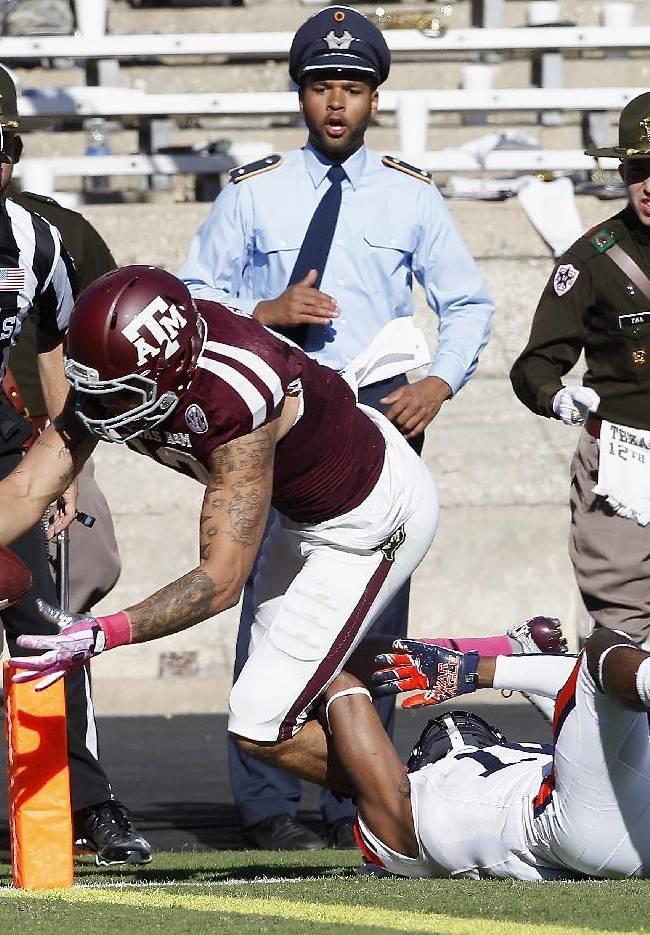 Texas A&M wide receiver Mike Evans (13) dives into the end zone for a touchdown in the quarter second quarter as Auburn defensive back Ryan White (19) cannot make the tackle during an NCAA college football game Saturday, Oct. 19, 2013, in College Station, Texas