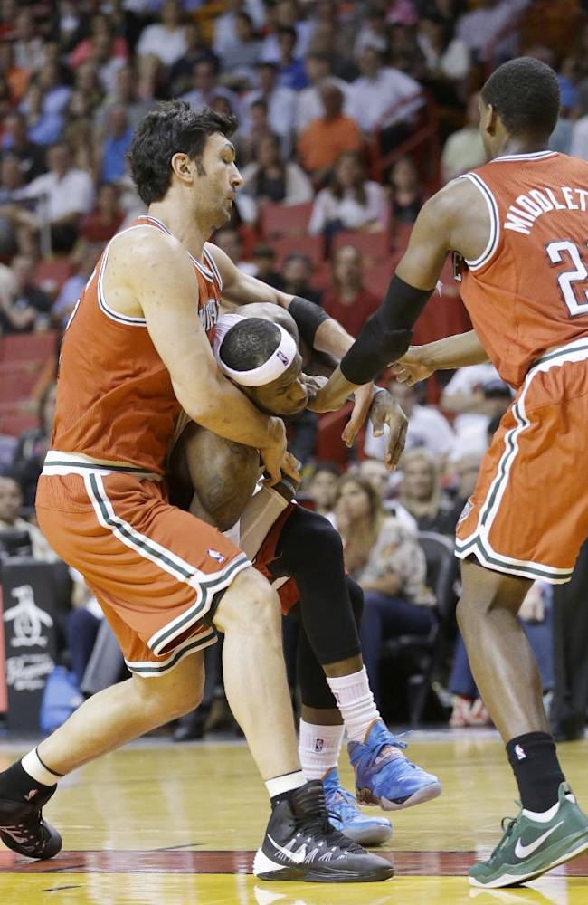 Miami Heat forward LeBron James, center, is fouled by Milwaukee Bucks center Zaza Pachulia, left, of Georgia, while going up to shoot against Pachulia and forward Khris Middleton (22) during the first half of an NBA basketball game on Wednesday, April 2, 2014, in Miami