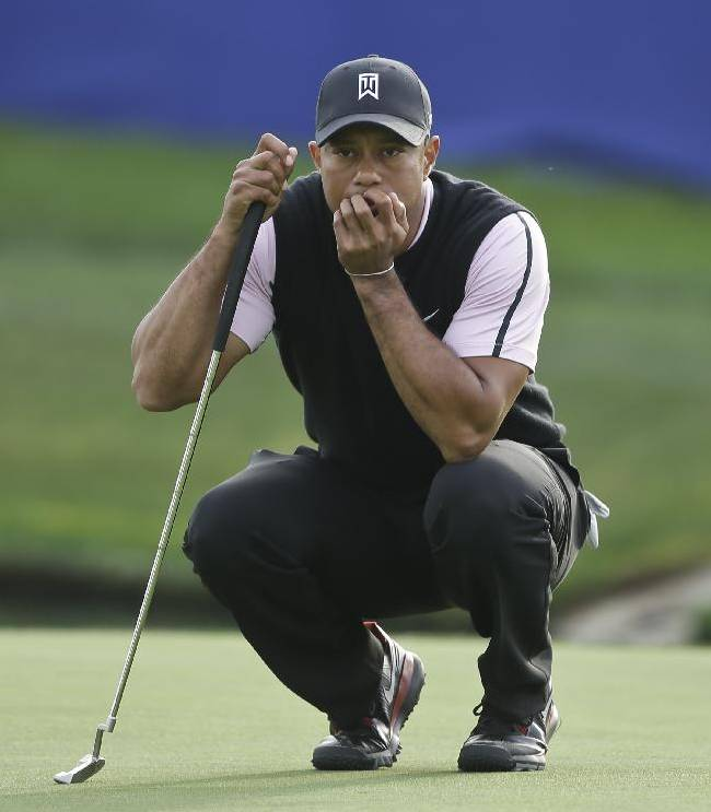 Tiger Woods examines his putt while waiting for his playing partners on the 18th green of the South Course at Torrey Pines during the first round of the Farmers Insurance Open golf tournament Thursday, Jan. 23, 2014, in San Diego