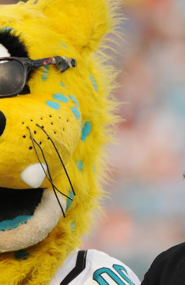 Jacksonville Jaguars owner Shad Khan scans the stands at EverBank Field as he stands next to the Jaguars mascot, Jaxon de Ville, during the kickoff presentation of the new scoreboards at the stadium Saturday evening, July 26, 2014, in Jacksonville, Fla. The Mega Event featured a soccer match, the unveiling of the new scoreboards and a concert by Carrie Underwood