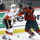 Calgary Flames' Paul Byron, left, and Minnesota Wild's Nate Prosser do some shoving as the puck rolls between them in the first period of an NHL hockey game, Monday, March 3, 2014, in St. Paul, Minn The Associated Press