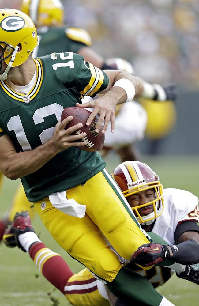 Washington Redskins' Josh Wilson sacks Green Bay Packers quarterback Aaron Rodgers during the second half of an NFL football game Sunday, Sept. 15, 2013, in Green Bay, Wis