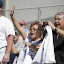 A woman calls out for her husband, right, to take a photo of Derek Jeter during batting practice before a spring training baseball game between the New York Yankees and the Tampa Bay Rays in Tampa, Fla., Sunday, March 9, 2014 The Associated Press