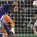 Anderlecht's Andy Najar heads the ball to score his team's first goal passing Arsenal's goalkeeper Emiliano Martinez, rear in orange, and Arsenal's Calum Chambers, right, during the Group D Champions League match between Anderlecht and Arsenal at Constant