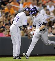 Colorado Rockies' Charlie Culberson (23) is greeted by third base coach Stu Cole (39) after he hit a home run against the Baltimore Orioles during the sixth inning of a baseball game, Friday, Aug. 16, 2013, in Baltimore. (AP Photo/Nick Wass)