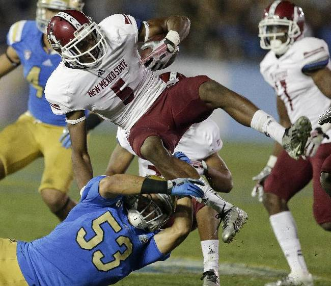 UCLA linebacker Ryan Hofmeister, bottom, brings down New Mexico State wide receiver Joseph Matthews during the second half of an NCAA college football game Saturday, Sept. 21, 2013, in Pasadena, Calif. UCLA won 59-13