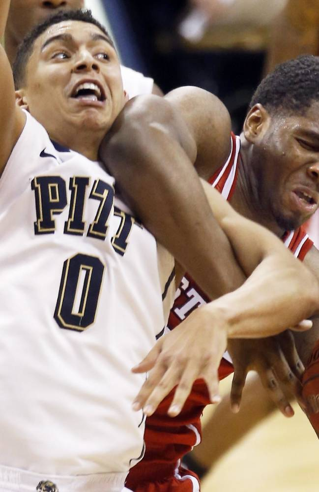 Pittsburgh's James Robinson (0) and North Carolina State's Lennard Freeman battle for a rebound during the second half of an NCAA college basketball game on Monday, March 3, 2014, in Pittsburgh. Robinson was called for a foul on the play. North Carolina State won 74- 67