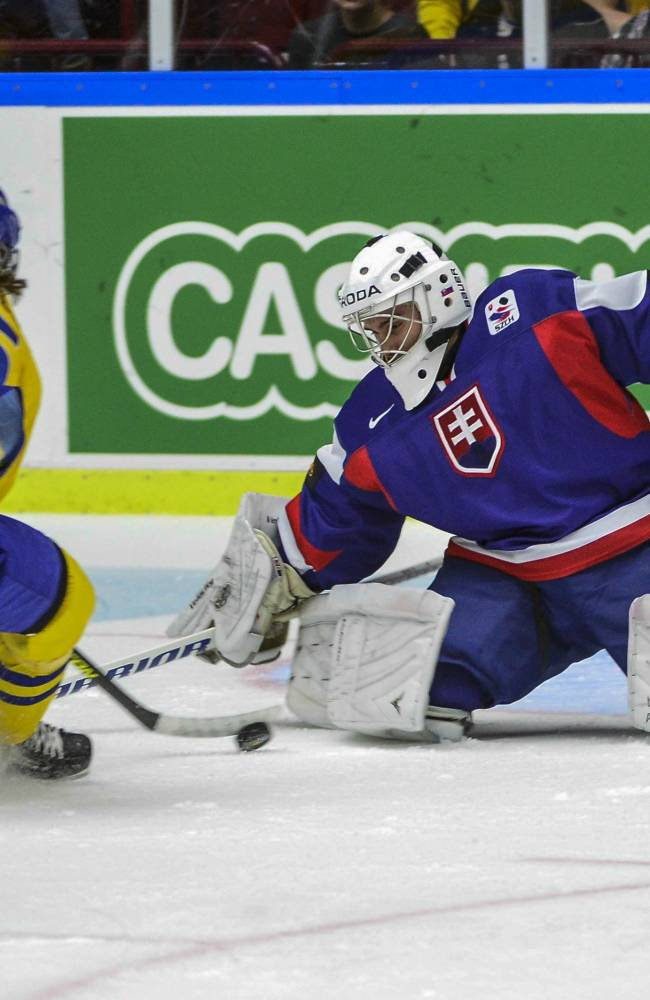Sweden's Sebastian Collberg, left, attempts to score past Slovakia's goalie Richard Sibol, during the World Junior Hockey Championships quarter final between Sweden and Slovakia at the Malmo Arena in Malmo, Sweden on Thursday, Jan. 2, 2014. (AP Photo / TT News Agency / Ludvig Thunman) SWEDEN OUT