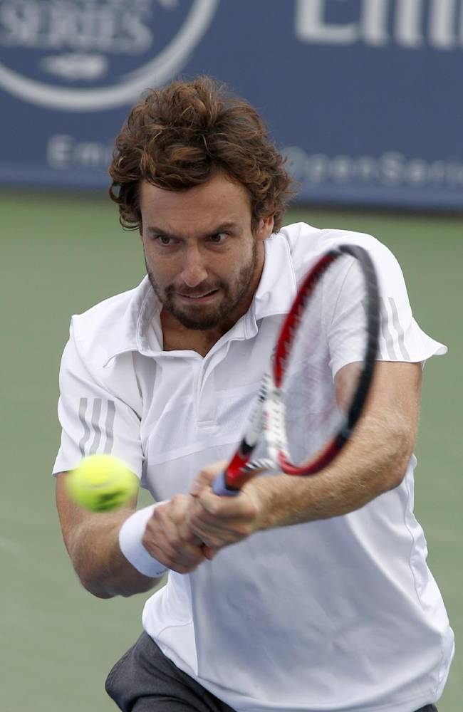 Ernests Gulbis, from Latvia, hits a backhand to Ivan Dodig, from Croatia, during a first round match at the Western & Southern Open tennis tournament, Tuesday, Aug. 12, 2014, in Mason, Ohio