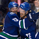 This Oct. 30, 2014, file photo shows Vancouver Canucks' Daniel Sedin, right, celebrating with his twin brother Henrik Sedin, both of Sweden, after scoring the winning goal against the Montreal Canadiens at an NHL hockey game in Vancouver. After the Canuck