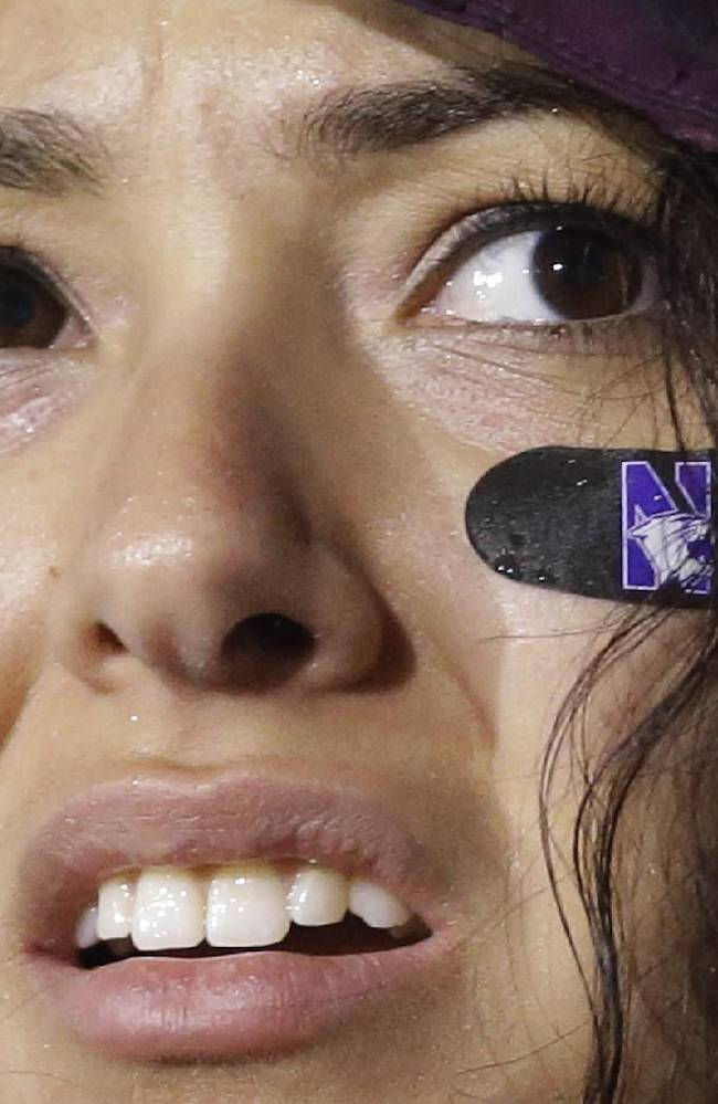 A Northwestern fan reacts as she looks at the scoreboard during the second half of Northwestern's NCAA college football game against Michigan in Evanston, Ill., Saturday, Nov. 16, 2013. Michigan won 27-19