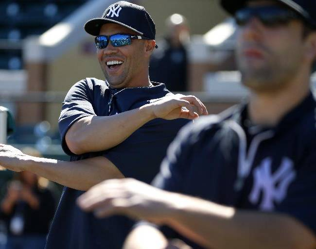 New York Yankees'  Carlos Beltran, left,  stretches before an exhibition spring training baseball game against the Detroit Tigers in Lakeland, Fla.,  Friday, Feb. 28, 2014