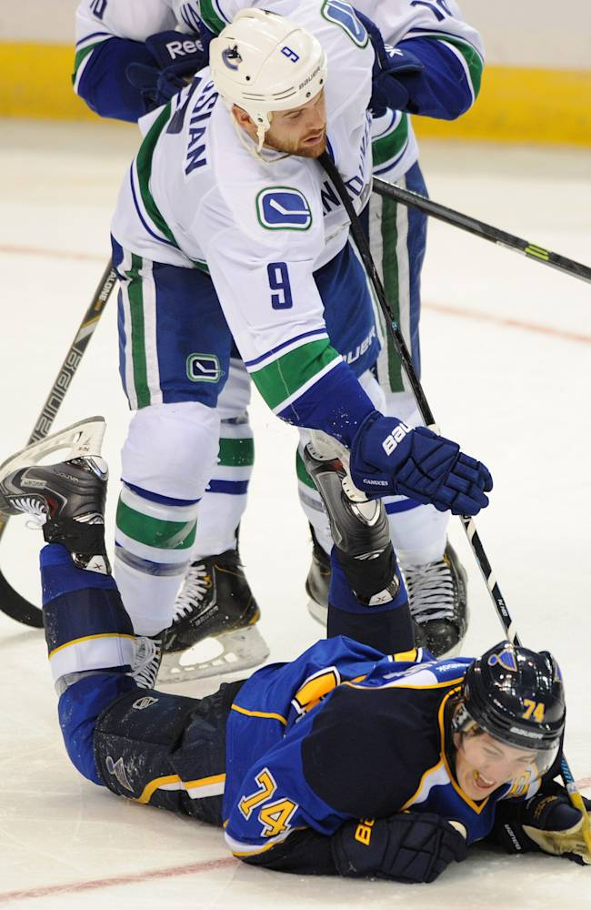 St. Louis Blues' T.J. Oshie (74) slides under Vancouver Canucks' Zack Kassian (9) during the third period of an NHL hockey game on Friday, Oct. 25, 2013, in St. Louis