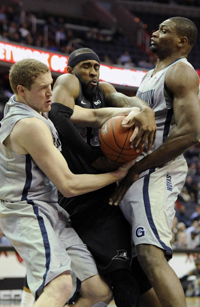 Georgetown forward Nate Lubick, left, and Moses Ayegba, right, battle for the ball against Providence forward LaDontae Henton, center, during the first half of an NCAA college basketball game, Monday, Feb. 10, 2014, in Washington