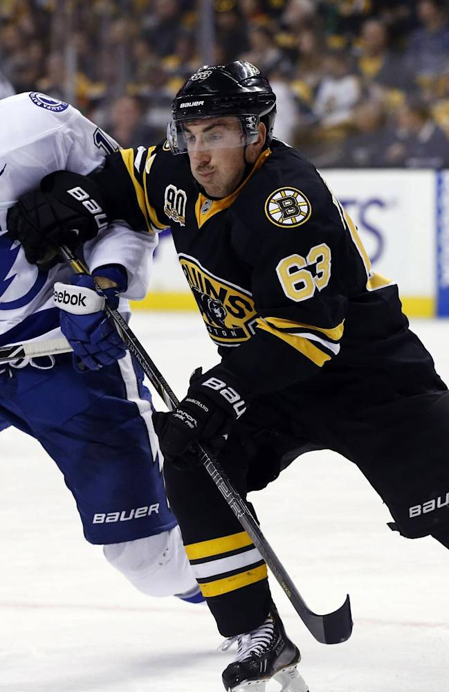 Boston Bruins left wing Brad Marchand (63) fights for position with Tampa Bay Lightning right wing Brett Connolly (14) during the third period of an NHL hockey game in Boston, Monday, Nov. 11, 2013. The Bruins won 3-0