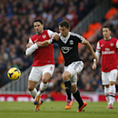 Arsenal s Mikel Arteta, left, competes for the ball with Southampton s Jay Rodriguez during the English Premier League soccer match between Arsenal and Southampton at the Emirates Stadium in London, Saturday, Nov. 23, 2013
