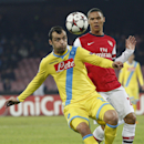 Napoli forward Goran Pandev of Macedonia, left, and Arsenal's Kieran Gibbs vie for the ball during a Champions League, group F soccer match, at the Naples San Paolo stadium, Italy, Wednesday, Dec. 11, 2013