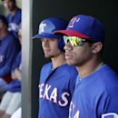 Seattle Seahawks quarterback Russell Wilson, right, stands by Texas Rangers' Brent Lillibridge in the dugout during a spring training exhibition baseball game against the Cleveland Indians, Monday, March 3, 2014, in Surprise, Ariz The Associated Press