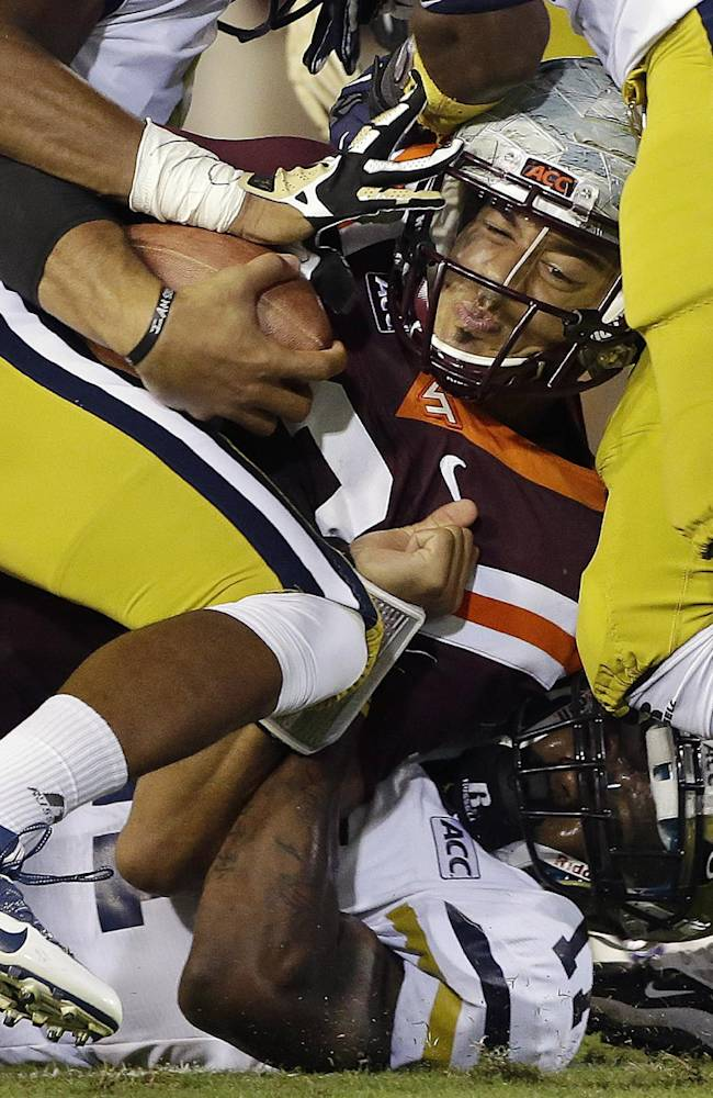 Virginia Tech quarterback Logan Thomas is stopped by the Georgia Tech defense after a short gain in the first half of an NCAA college football game on Thursday, Sept. 26, 2013, in Atlanta