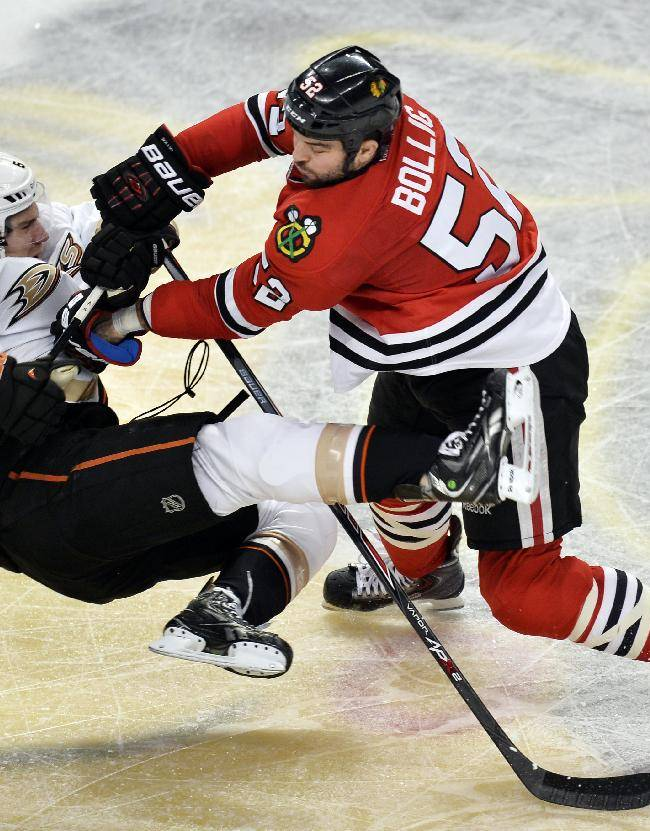 Chicago Blackhawks left wing Brandon Bollig, right, takes out Anaheim Ducks defenseman Ben Lovejoy during the third period of an NHL hockey game Friday, Dec. 6, 2013, in Chicago. The Ducks won 3-2 in a shootout