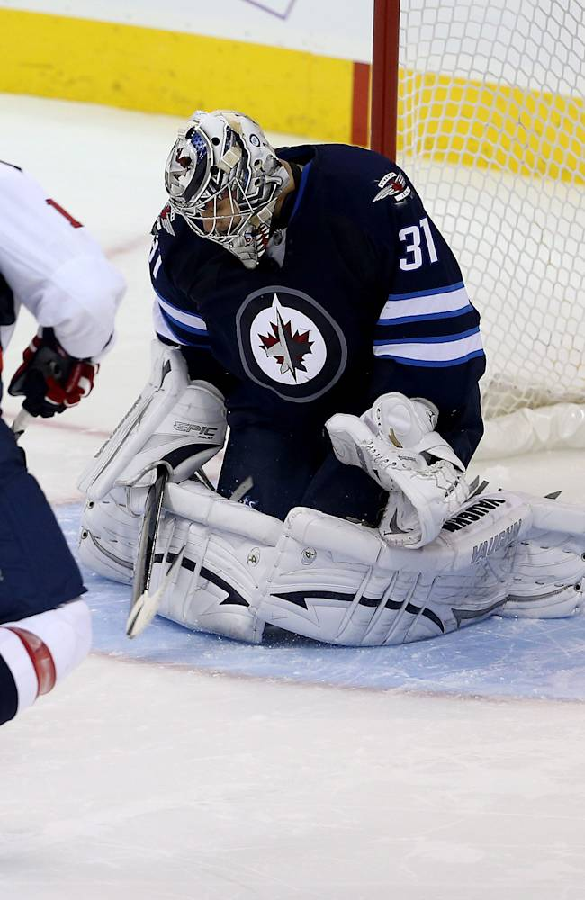 Washington Capitals' Martin Erat (10) scores the game-winning goal in a shootout against Winnipeg Jets' goaltender Ondrej Pavelec (31) during an NHL hockey game in Winnipeg, Manitoba, Tuesday, Oct. 22, 2013. The Capitals won 5-4 in a shootout