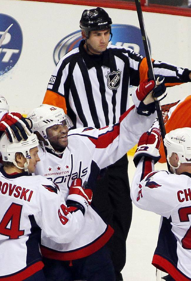 Washington Capitals' Joel Ward, center, is surrounded by teammates after scoring his second goal as Philadelphia Flyers goalie, Ray Emery, rear, approaches the referee to complain that his face mask was knocked off in the third period of an NHL hockey game Friday, Nov. 1, 2013, in Philadelphia. The Capital won 7-0
