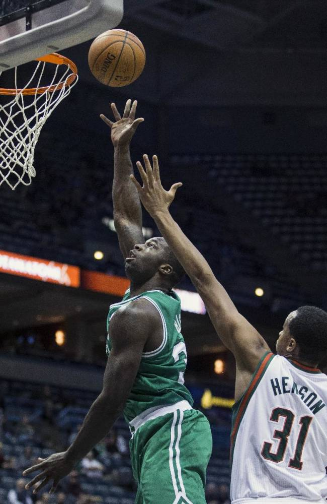Milwaukee Bucks' John Henson tries to stop Boston Celtics' Brandon Bass, left, during the first half of an NBA basketball game, Monday, Feb. 10, 2014, in Milwaukee