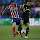 Atletico's Diego Godin, left, vies for the ball with Chelsea's Fernando Torres, right, during the Champions League semifinal first leg soccer match between Atletico Madrid and Chelsea at the Vicente Calderon stadium in Madrid, Spain, Tuesday, April 22, 20
