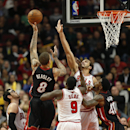 Miami Heat forward Michael Beasley (8) shoots over Chicago Bulls forward Luol Deng (9) and center Joakim Noah during the second half of an NBA basketball game in Chicago, Thursday, Dec. 5, 2013. The Bulls defeated the Heat 107-87 The Associated Press
