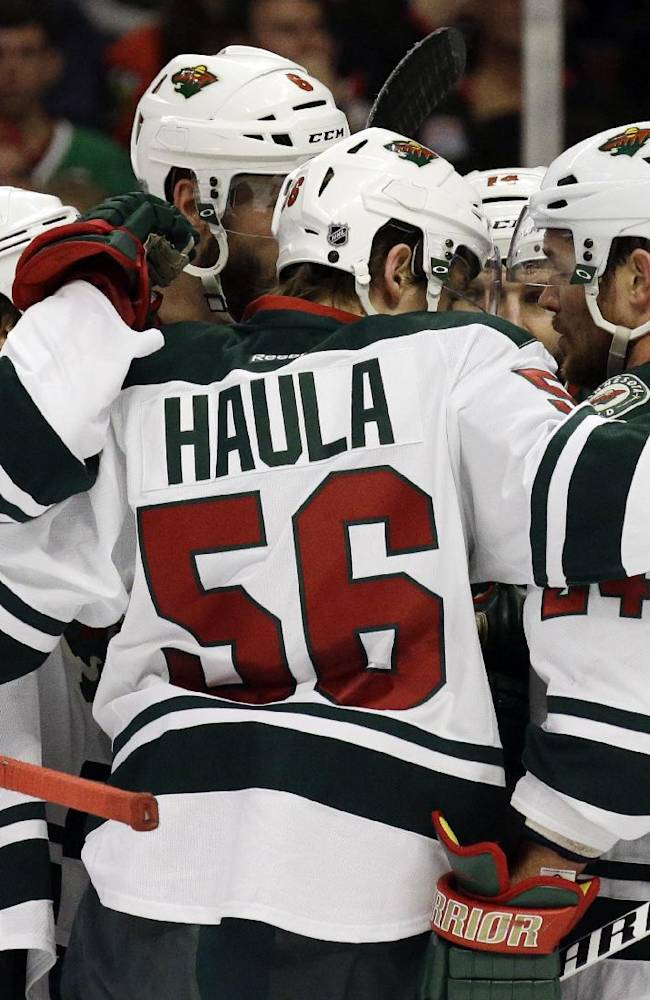 Minnesota Wild's Erik Haula (56) celebrates with teammates after scoring his goal against the Chicago Blackhawks during the first period  in Game 5 of an NHL hockey second-round playoff series in Chicago,Sunday, May 11, 2014