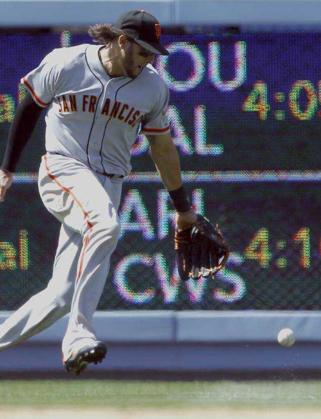 The ball drops next to San Francisco Giants left fielder Michael Morse for a single hit by Los Angeles Dodgers' Yasiel Puig in the sixth inning of a baseball game on Saturday, May 10, 2014, in Los Angeles