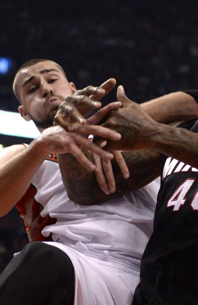 Miami Heat's Udonis Haslem, (40), and Toronto Raptors' Jonas Valanciunas battle for a rebound during first half of an NBA basketball game, Tuesday, Nov. 5, 2013 in Toronto
