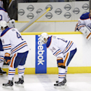 Edmonton Oilers goalie Ben Scrivens (30) waits on the bench as Jordan Eberle (14), Taylor Hall (4) and Keith Aulie (22) leave the ice after the Nashville Predators won 1-0 in overtime in an NHL hockey game Thursday, Nov. 27, 2014, in Nashville, Tenn The A