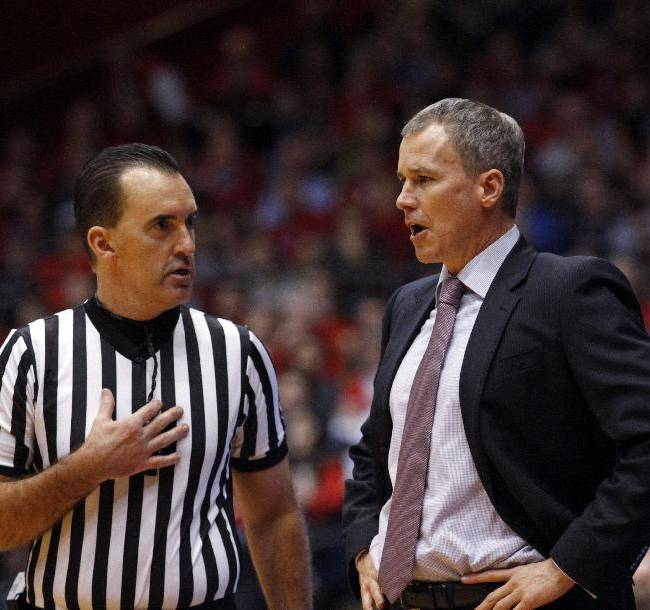 Southern California coach Andy Enfield, right, talks with a referee in the first half of an NCAA college basketball game against Dayton, Sunday, Dec. 22, 2013, in Dayton, Ohio