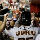 San Francisco Giants' Brandon Crawford, right, gets high-fives from teammates after he scored a run against the Arizona Diamondbacks during the third inning of an opening day baseball game, Monday, March 31, 2014, in Phoenix The Associated Press