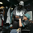 In this Oct. 18, 2013 photo, Philadelphia eagles quarterback Michael Vick give seven-year-old Justin Perales a fist bump during a tour of the Eagles training facility in Philadelphia. Four years after his release from prison, Vick is one of the NFL's mos