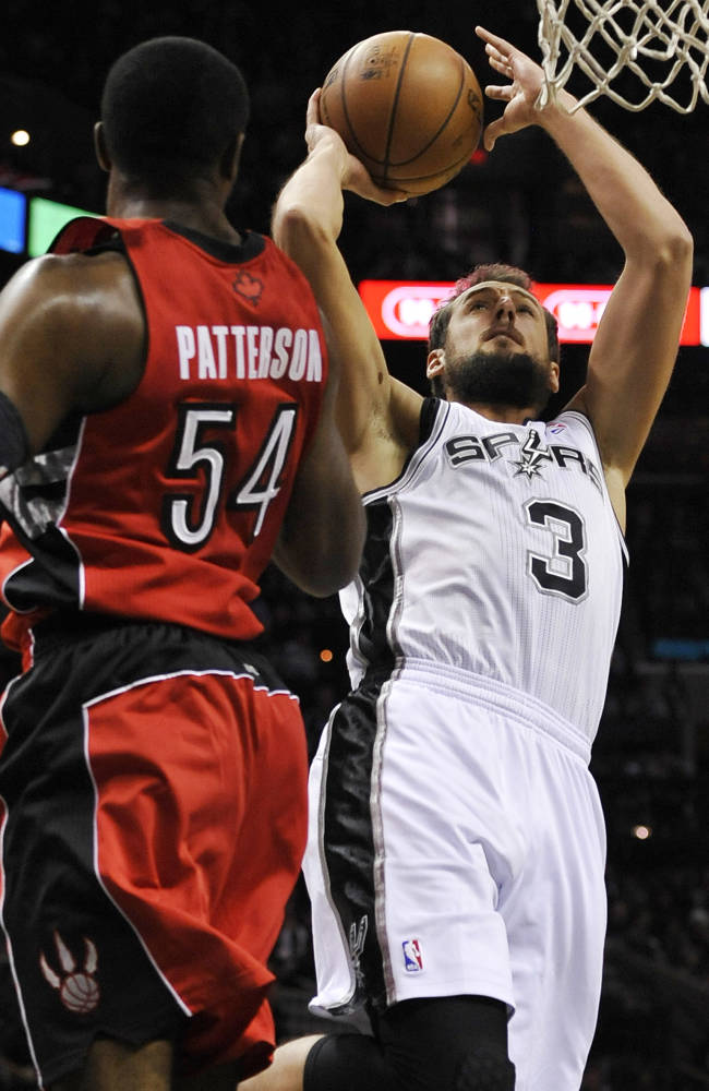 San Antonio Spurs guard Marco Belinelli, right, of Italy, shoots against Toronto Raptors forward Patrick Patterson during the first half of an NBA basketball game on Monday, Dec. 23, 2013, in San Antonio. San Antonio won 112-99