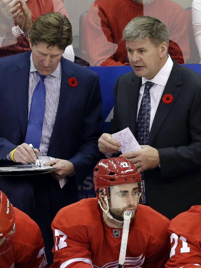 In this Nov. 9, 2013, file photo, Detroit Red Wings coach Mike Babcock, left, and assistant coach Bill Peters talk during the overtime period of an NHL hockey game against the Tampa Bay Lighting in Detroit. The Carolina Hurricanes have hired Peters as their new coach on Thursday, June 19, 2014