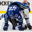 Vancouver Canucks' Daniel Sedin, top, of Sweden, falls on top of Los Angeles Kings' Dustin Brown during the first period of an NHL hockey game Saturday, April 5, 2014, in Vancouver, British Columbia The Associated Press