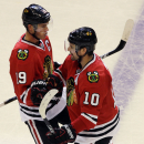 Chicago Blackhawks left wing Patrick Sharp (10) celebrates with center Jonathan Toews (19) after scoring a goal against the Buffalo Sabres during the third period of an NHL hockey game in Chicago, Saturday, Oct. 11, 2014. The Blackhawks won 6-2 The Associ