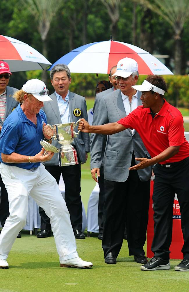 Miguel Angel Jimenez, left, of Spain shares a light moment with Thongchai Jaidee, right, of Thailand while Malaysia's Prime Minister Najib Razak looks on during the third round of the Eurasia Cup golf tournament at the Glenmarie Golf and Country Club in Subang, Malaysia, Saturday, March 29, 2014