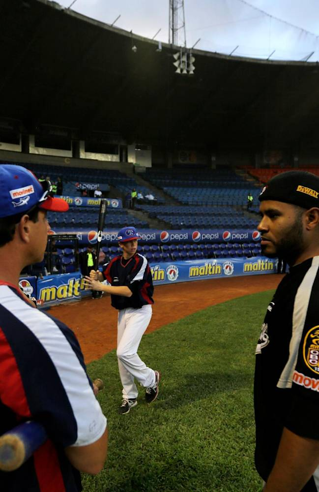 In this Nov. 27, 2013 photo, Anthony DeFrancesco, center, son of Tiburones' head coach Tony DeFrancesco, left, practices his baseball swing as his father speaks with a player prior to a baseball game against rival Leones, at Estadio Universitario in Caracas, Venezuela. In the land of Hugo Chavez, a place in many ways hostile to Americans owing to its reputation for rampant crime, a crumbling economy and an anti-capitalist government, hitters and hurlers from across the U.S. are thriving as they try to impress big league scouts who come for the winter season