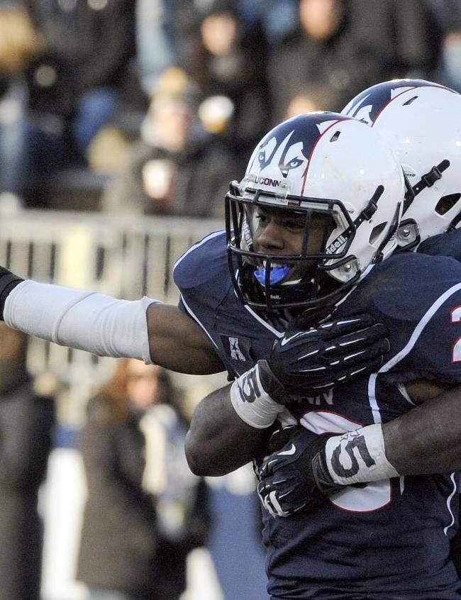 Connecticut cornerback Taylor Mack (29) and linebacker Jefferson Ashiru (32) celebrate  after Mack intercepted a pass during the second half of Connecticut's 28-17 victory Rutgers in an NCAA college football game in East Hartford, Conn., on Saturday, Nov. 30, 2013